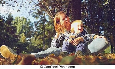 young mother playing with her baby. Mom and son sitting on the grass in a park in autumn in slowmotion. 1920x1080