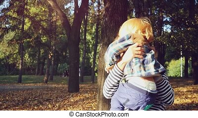 young mother playing with her baby. Mom and son sitting on the grass in a park in autumn in slowmotion.