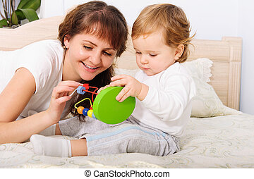 Young mother playing with her baby son