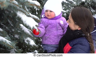 young mother playing with her daughter outdoors at winter time and shakes snow from the trees