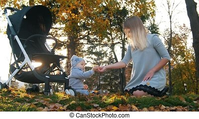 Young mother playing with her little baby son. Playing with autumn leaves.