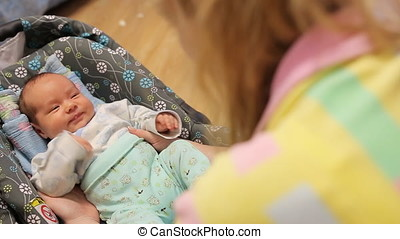 Young mother playing with her newborn baby