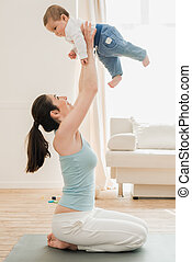 Young mother playing with her son at home in sunny day. Woman holding child on outstretched hands