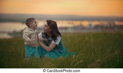 Young mother plays with her baby on the grass, the child is...