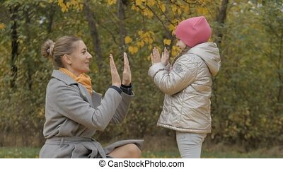 young mother plays with her little daughter on a green background