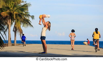 young mother plays with small blonde daughter on pier