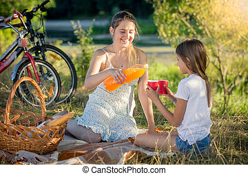 Young mother pouring juice from bottle into daughter's cup on picnic at park