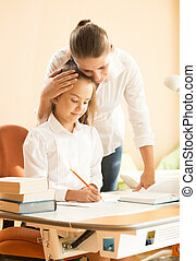young mother praising daughter doing homework at desk -...