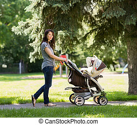 Young Mother Pushing Stroller In Park - Full length portrait...