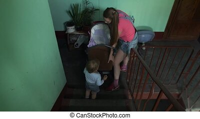 Young mother put down baby carriage from stairs. Motherhood....