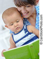 young mother reading a book to her baby