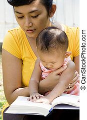 young mother reading while babysitting