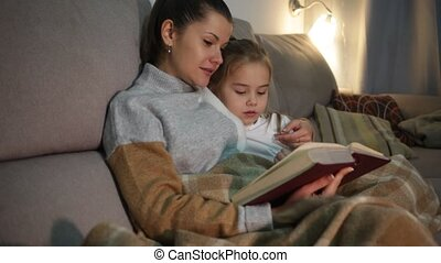 Young woman reading an interesting book with small daughter
