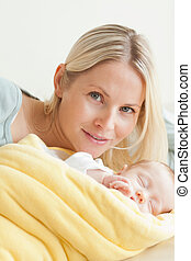Young mother relaxing next to her sleeping baby
