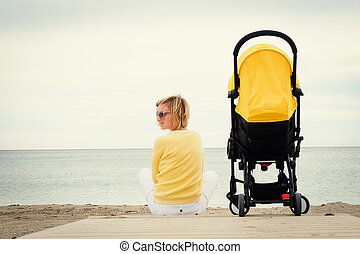 Young mother relaxing on beach with baby stroller