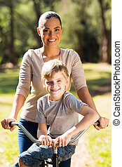 young mother riding a bicycle with her son outdoors