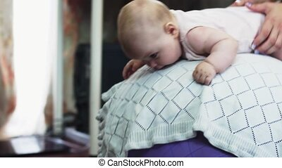 Young mother roll adorable baby on inflatable purple fitness ball. Exercise.