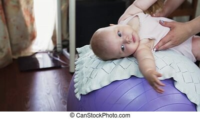 Young mother roll little baby on inflatable purple fitness ball. Exercise. Happy