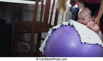 Young mother roll little baby on inflatable purple fitness ball. Exercise. Child