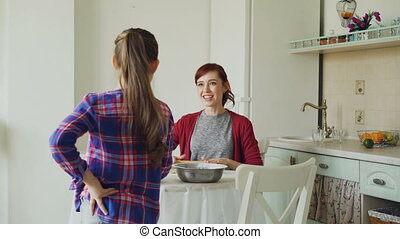Young mother rolling dough while cooking and her funny daughter walking around and singing with comb dancing in the kitchen on weekend. Family, food, home and people concept