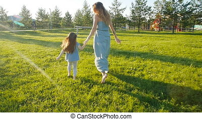 Young mother running with her daughter outdoors in slow motion
