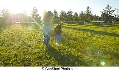 Young mother running with her daughter outdoors in slow...