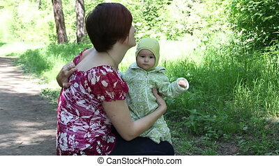 Young mother shows the child doves in park