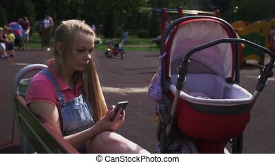Young mother sit on bench on playground, tapping on smartphone. Baby carriage.