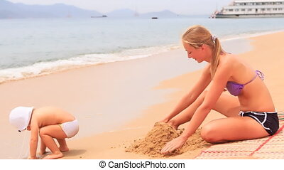 young mother sits on mat builds sand castle against vessel