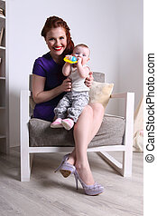 Young mother sits with her little baby on armchair in room at home