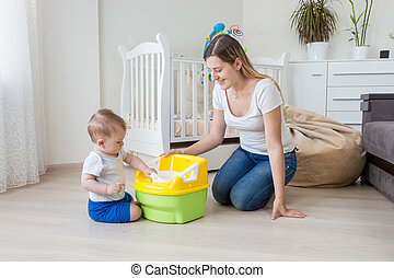 Young mother sitting on floor at living room and teaching ...