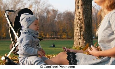 Young mother sitting on the grass and playing with her little baby. Waving hand to the cameraman