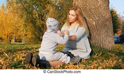 Young mother sitting on the grass with her little baby, smiling. Waving hand to the cameraman.