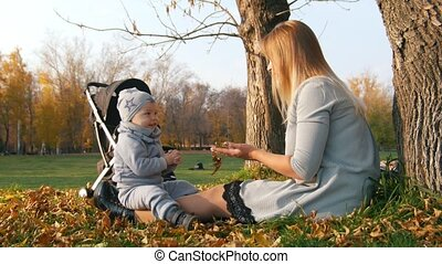 Young mother sitting on the grass with her little baby. Waving hand to the cameraman.