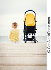 Young mother sitting outdoor with stroller