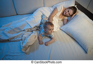 Young mother sleeping with her baby boy in bed