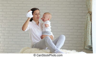 Young mother soothes a crying little baby at home in the bedroom. Close-up.