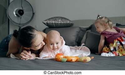 Young mother spending time with two children in the bedroom.