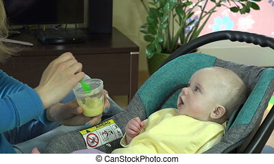 young mother spoon feeding her baby girl. 4K