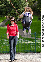 Young mother swing a child in playground