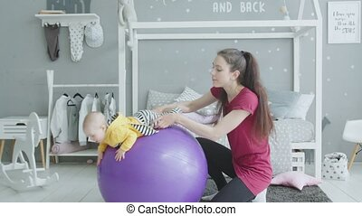 Young mother swinging baby girl on fitball at home