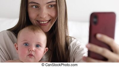 Young mother taking selfie with baby - Beautiful young woman...