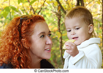Young mother talks with her little daughter with yellow leaf in hand at autumn. Focus on girl