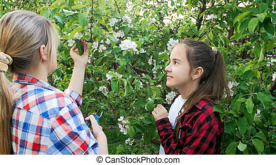 Young mother teaching her daughter how to cut branches with garden cutters
