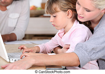 young mother teaching her daughter how to use computer