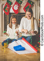 Young mother teaching her daughter how to wrap Christmas presents
