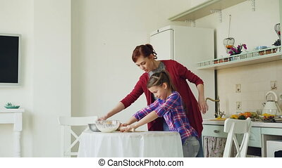 Young mother teaching her little cute daughter rolling dough while cooking together in the kitchen at home on holidays. Family, food and people concept