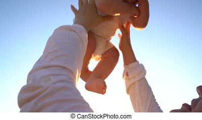 Young mother throwing baby boy in the air at the beach, slow...