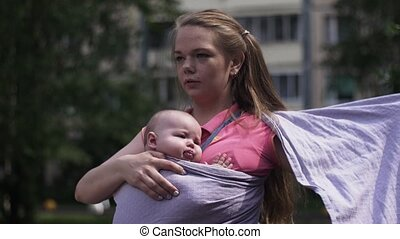 Young mother tie baby sling holding little child....