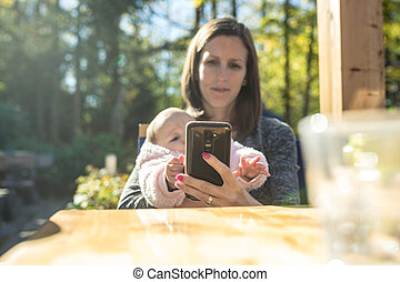 Young mother using mobile phone while with her daughter